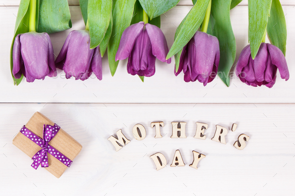 Bouquet of purple tulips and gift for mother's day on white boards - Stock Photo - Images