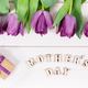 Bouquet of purple tulips and gift for mother's day on white boards - PhotoDune Item for Sale