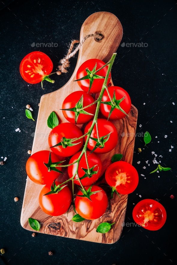 a bunch of fresh organic cherry tomatoes with sea salt and basil in olive cutting board - Stock Photo - Images