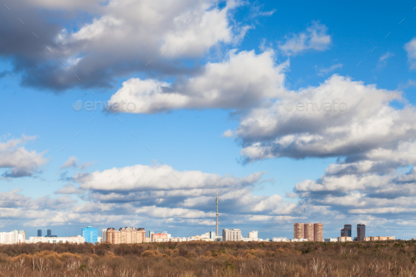 white clouds in blue sky over woods in spring day - Stock Photo - Images