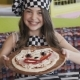 The Young Girl Shows a Pizza with Smiles at Camera - VideoHive Item for Sale