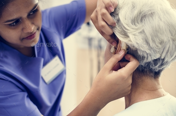 An elderly woman with hearing aid - Stock Photo - Images