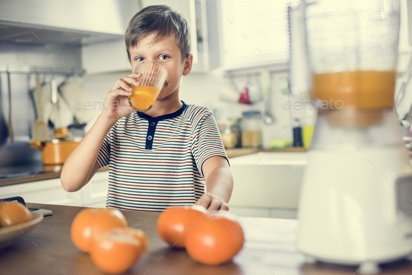 Young Caucasian boy drinking orange juice - Stock Photo - Images