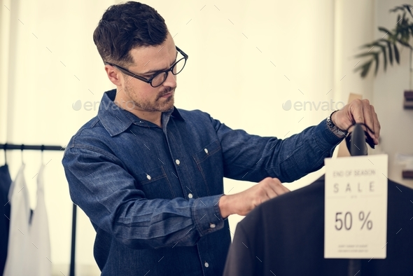 Man working in retail cloth shop - Stock Photo - Images