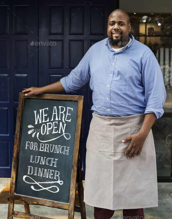 A cheerful business owner standing with open blackboard - Stock Photo - Images