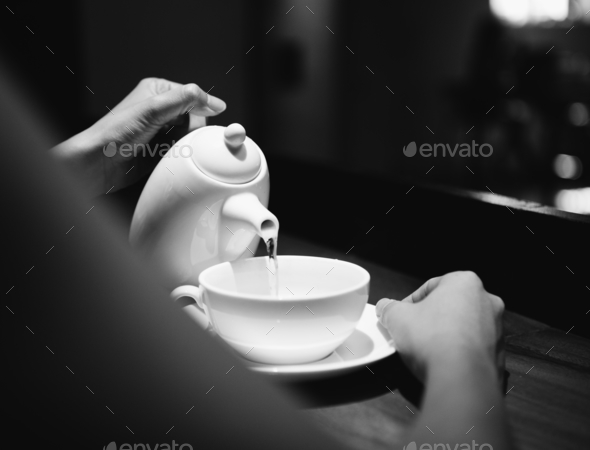 Woman holding a pot and pouring a drink - Stock Photo - Images