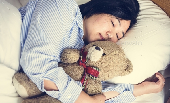 A woman in bed with a teddy bear - Stock Photo - Images