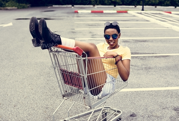 An African Descent woman sitting in a shopping trolley - Stock Photo - Images