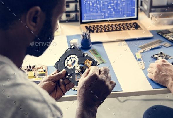 Technicians working on computer hard disk - Stock Photo - Images