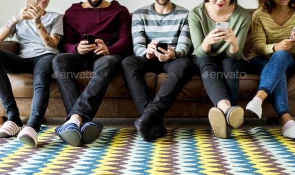 Group of people using mobile phone on couch - Stock Photo - Images