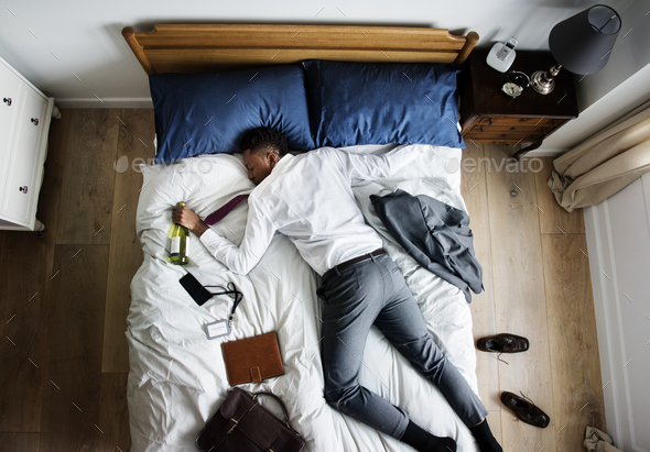 Drunk African American business man falling asleep as soon as he - Stock Photo - Images