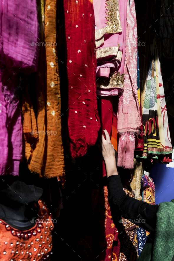 Woman choosing colorful sari in the market - Stock Photo - Images