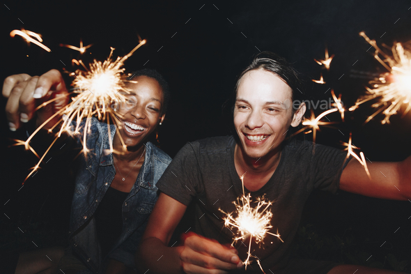 Friends celebrating with sparklers in the night - Stock Photo - Images
