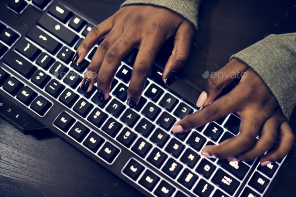 Closeup of hands working on computer keyboard - Stock Photo - Images
