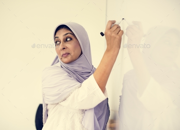 Muslim teacher writing on a white board - Stock Photo - Images