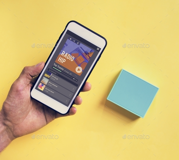 Hand holding smartphone connect to bluetooth speaker - Stock Photo - Images