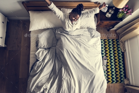 African American woman on bed waking up in the morning - Stock Photo - Images