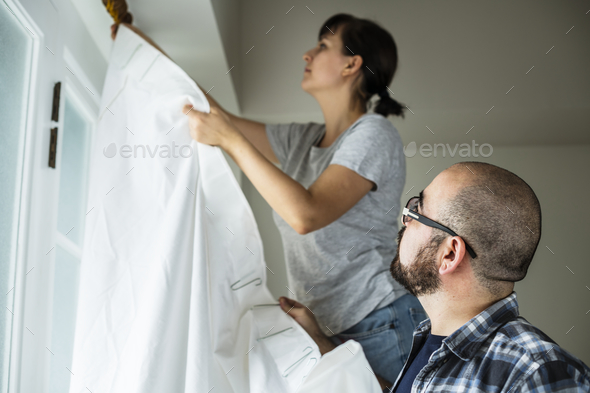 People installing window curtain - Stock Photo - Images