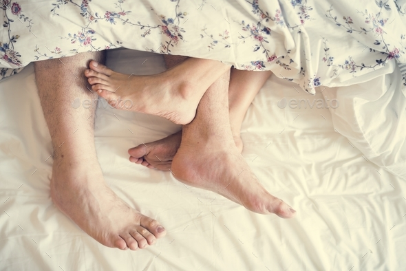 Aerial view of legs on bed - Stock Photo - Images