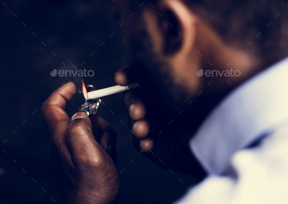 Rear view of man lighting a cigarette - Stock Photo - Images