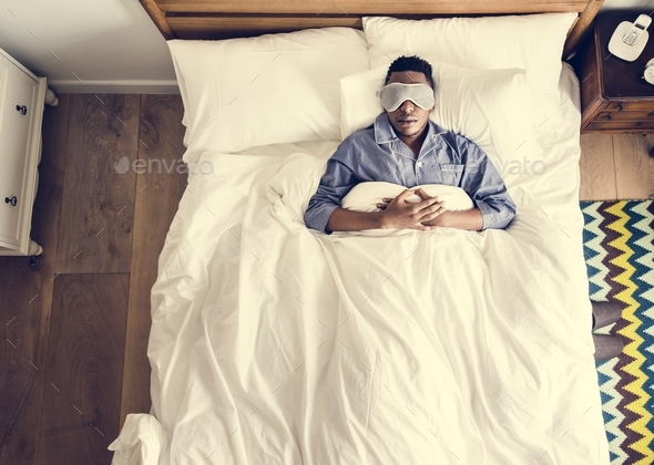 Black man sleeping on bed with eye mask - Stock Photo - Images