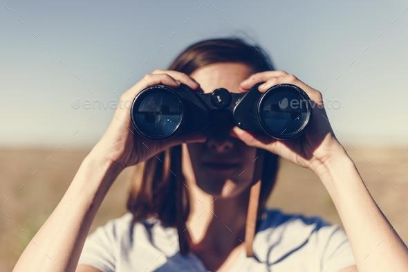 Traveler spying through binoculars - Stock Photo - Images