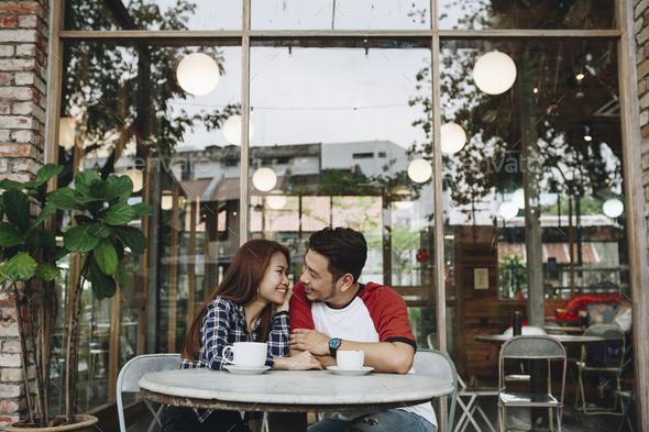 Lovely asian couple having coffee - Stock Photo - Images