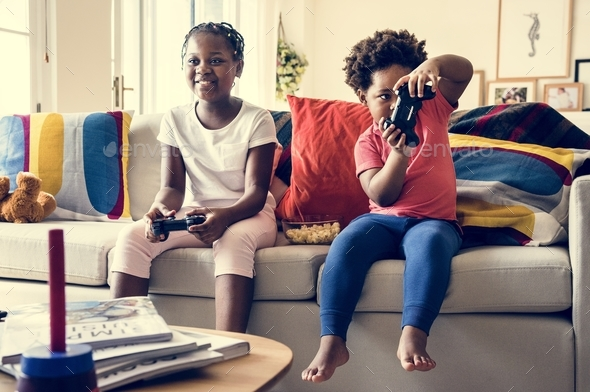 Siblings are playing game together - Stock Photo - Images