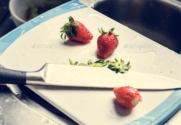 Closeup of fresh strawberries on cutting board with knife at sink - Stock Photo - Images