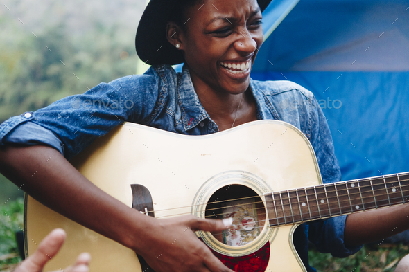 African American woman playing a guitar at a campsite - Stock Photo - Images