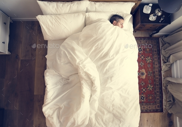 French man sleeping alone on bed - Stock Photo - Images