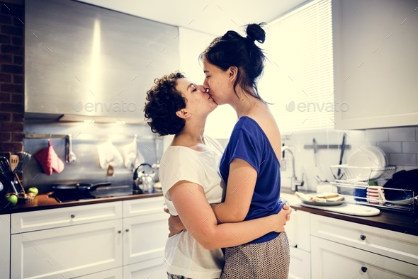 Lesbian couple kissing in the kitchen - Stock Photo - Images