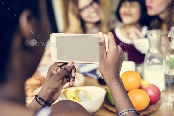 Closeup of mobile phone taking photo of diverse women - Stock Photo - Images