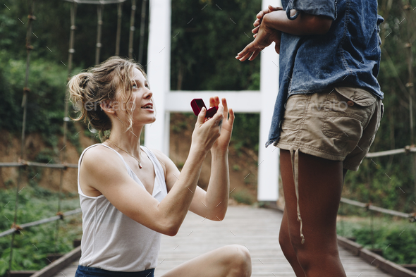 Woman proposing to her happy girlfriend outdoors love and marriage concept - Stock Photo - Images
