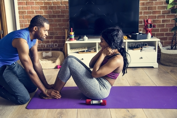 Black couple exercise at home together - Stock Photo - Images