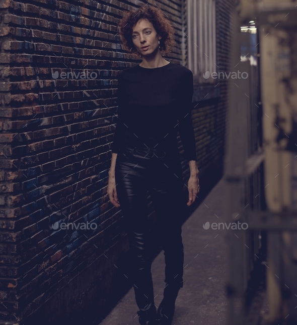 Woman walking through an alley - Stock Photo - Images