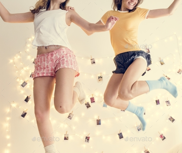Caucasian women jumping on the bed together - Stock Photo - Images