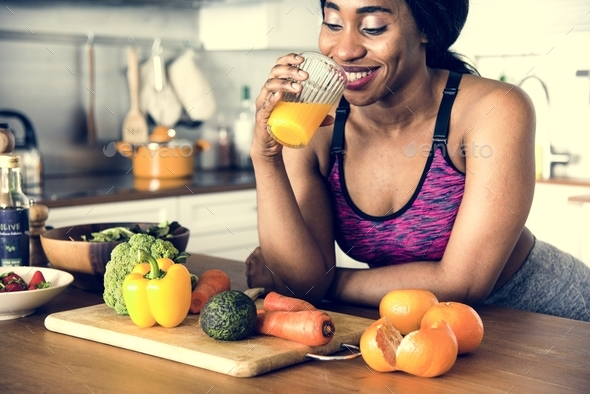 Black woman is drinking orange juice - Stock Photo - Images