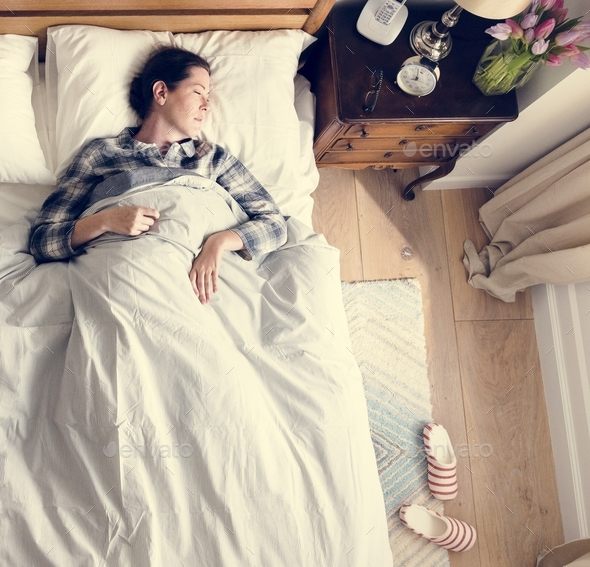 Caucasian woman sleeping on bed - Stock Photo - Images