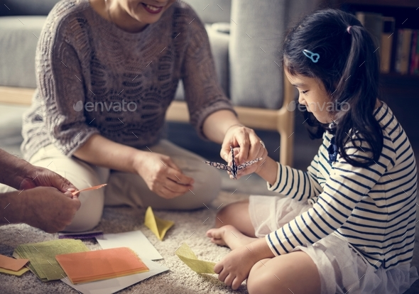 Japanese kid playing with an origami - Stock Photo - Images