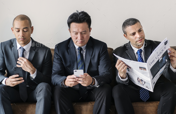 Businessmen working on phone and reading newspaper - Stock Photo - Images