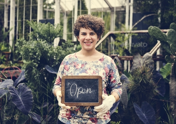 Garden shop owner holding an open sign - Stock Photo - Images