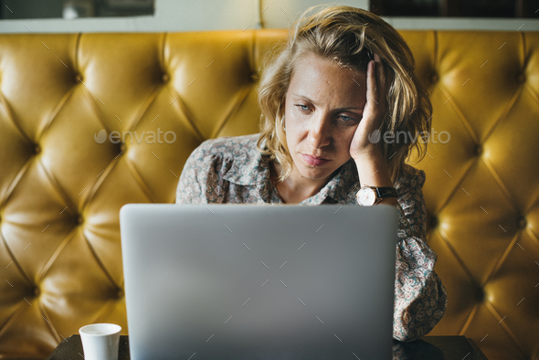 Blond woman working on her laptop at a cafe - Stock Photo - Images