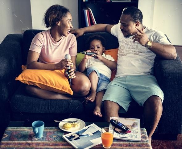 Black family enjoy singing karaoke - Stock Photo - Images