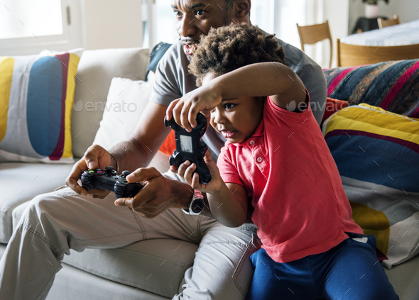 Dad and son playing game at living room together - Stock Photo - Images