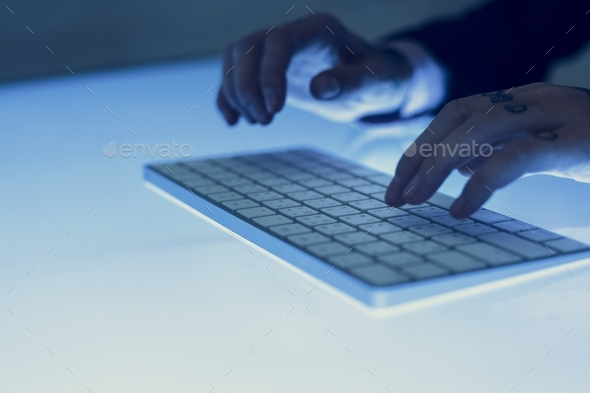 Hands with tattoo typing on a keyboard - Stock Photo - Images