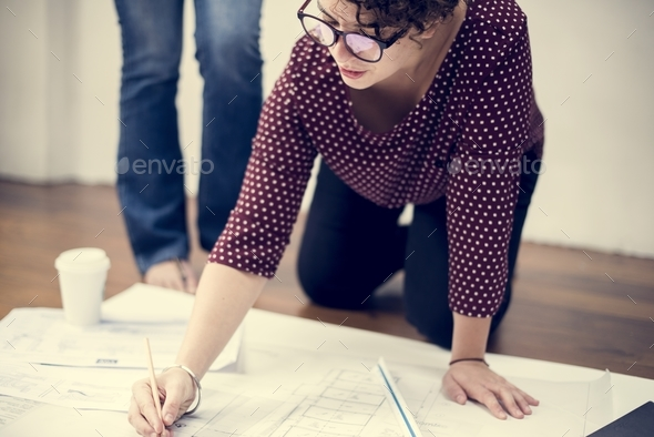 Woman working on drawing a plan - Stock Photo - Images