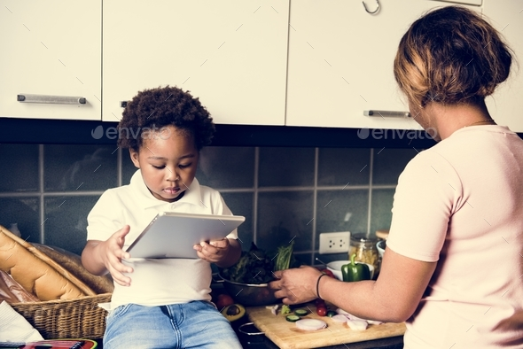 Black kid using tablet while mother cooking in the kitchen - Stock Photo - Images