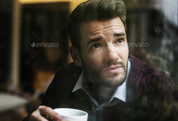 Contemplating man looking out the window - Stock Photo - Images