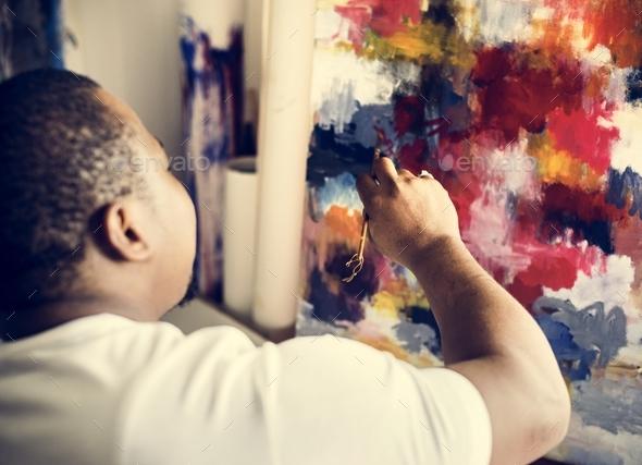 Black artist man doing his art work - Stock Photo - Images